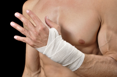 Closeup of shirtless male athlete with injured wrist bandaged in sports wrap on black background Stock Photo - 17945274