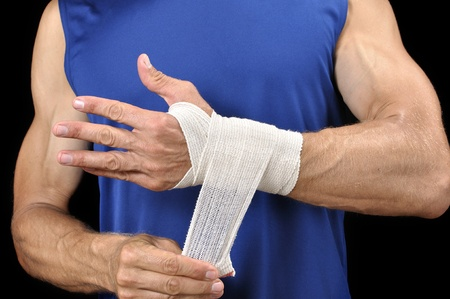 Athletic man in blue shirt wraps his wrist with sports wrap on black background Stock Photo - 17945270