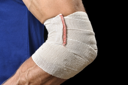 elbow bandage support: Closeup of atletic mans elbow bandaged with sports wrap on black background