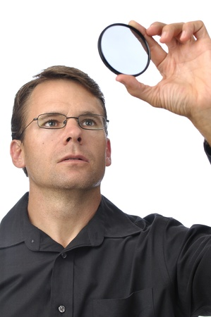 a round of inspection: Photographer holds up circular polarizer filter to check for dirt on white background Stock Photo