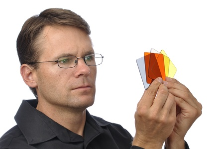 colored gels: Handsome male photographer holds and inspects colored square filters on white background Stock Photo