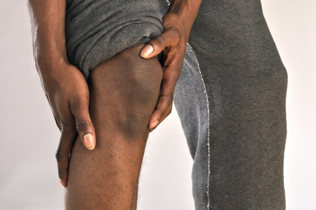 on hands and knees: Closeup of African American man clutching injured knee Stock Photo