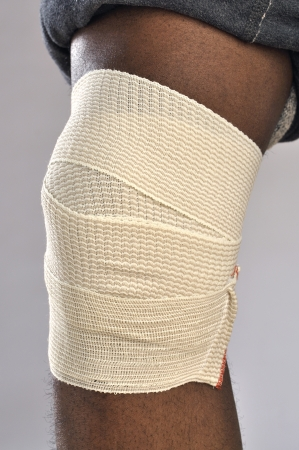 Closeup of injured knee with sport wrap on gray background photo