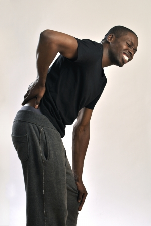Athletic African American man suffers severe back pain on gray background