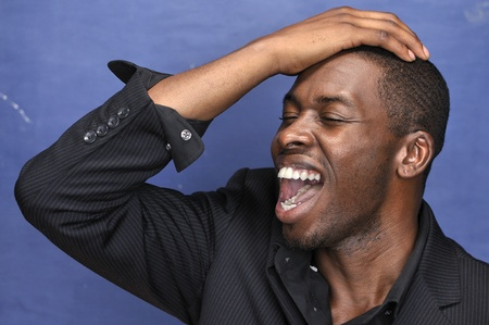 Young handsome black man in designer shirt yells with excitement on blue background Stock Photo - 18226252