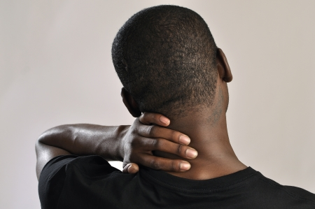 back ache: Closeup of man rubbing his neck with hand as he aches with pain in the neck on grey background