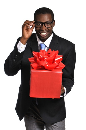 dweeb: Young black nerdy businessman with glasses delivers gift with big red bow on white background