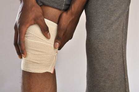 throb: Closeup of male athlete clutching knee wrapped in sports bandage on grey background Stock Photo