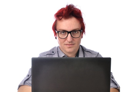interrupted: Serious young office worker interrupted in his work looks at camera over computer screen on white background