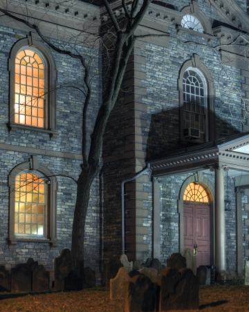 Exterior facade of scary haunted church with graveyard at night photo