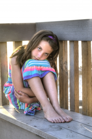 little girl barefoot: Pretty little girl with solemne expression sits on bench with arms wrapped around legs and head lying on knees at beach Stock Photo