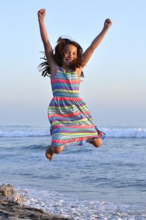 petite fille avec robe: Jolie jeune fille saute de joie en l'air sur le sable à la plage