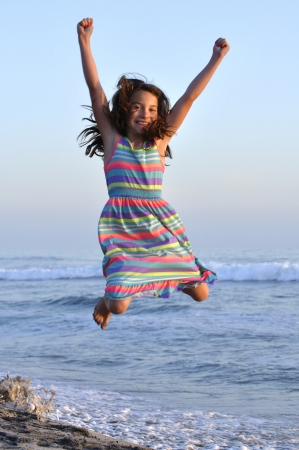 little girl dress: Pretty young girl jumps with joy in the air over the sand at the beach Stock Photo