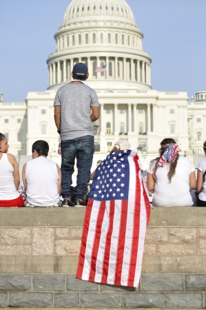Washington D.C. - April 10, 2013: Demonstrators gather in front of the U.S. capitol and show their patriotism during a rally for immigration reform on April 10, 2013.