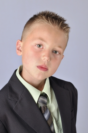 Headshot of handsome young serious business boy in suit on gray background photo