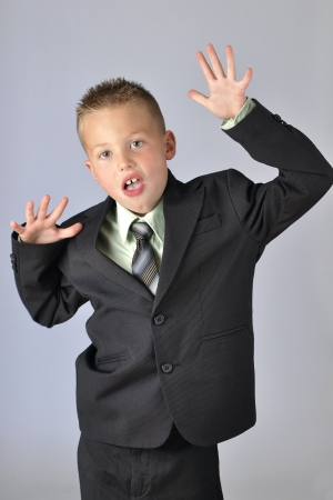 7 year old boys: Young boy in business suit makes silly gestures and facial expressions on gray background Stock Photo