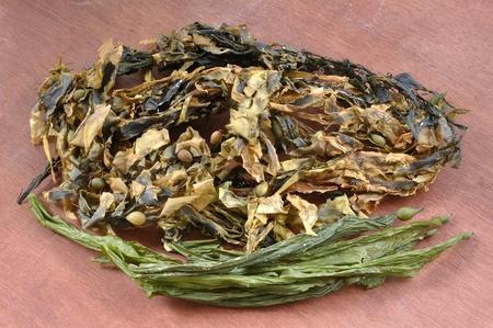 alga marina: Surtido de algas kelp seco destinado como alimento nutricional en el vector marrón