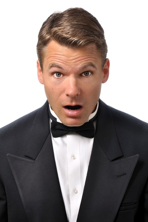 baffled: Closeup of handsome Caucasian man in tuxedo with look of surprise on face with white background Stock Photo