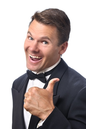 Handsome Caucasian man in black tuxedo gives a thumbs up and a big happy smile with white background