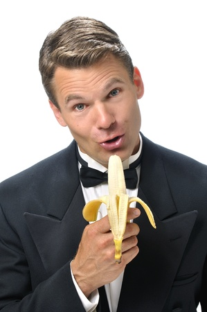 talk show: Portrait of handsome male Caucasian host in black tuxedo singing into a banana microphone with white background