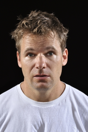 losers: Mug shot of Caucasian man with messy blond hair in white t-shirt on black background Stock Photo