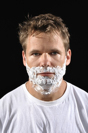 Closeup of handsome Caucasian man with shaving cream on face on black background  photo