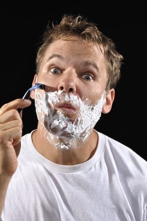 Handsome Caucasian man with messy bed head hair makes funny face while shaving his cheek on black background photo