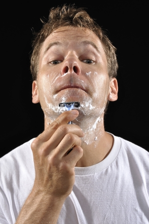 Portrait of Caucasian man shaving chin with sharp razor on black background photo