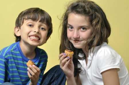 eight years old: Two young children being silly putting chocolate frosting on their lips while eating cupcakes Stock Photo