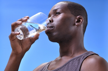 inferior: Closeup inferior angle of young athletic black man drinking clean pure water from a glass with blue sky background