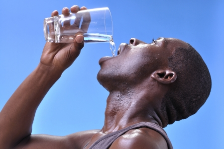 man drinking water: Closeup of thirsty sweaty young athletic black man pouring clean pure water into mouth from glass on blue sky background Stock Photo