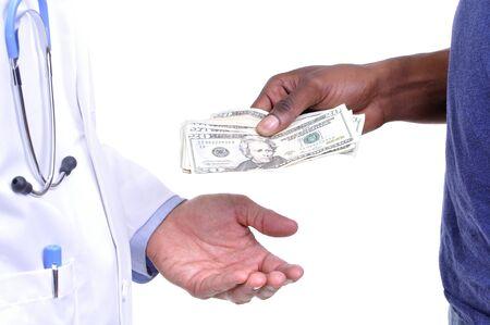 Close-up van de hand van de onverzekerde patiënt die contant betalen aan de hand van de arts het dragen lab jas op een witte achtergrond