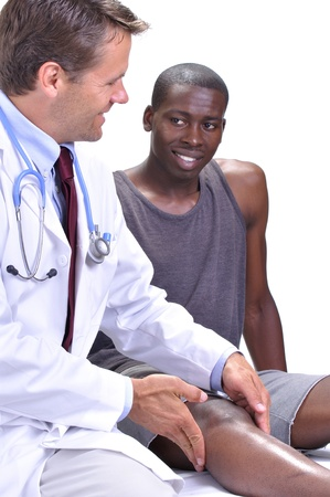 Medical doctor feels and checks the knee of his young athletic patient while they exchange a smile on white background