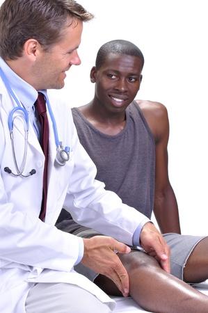 de rodillas: M�dico que se siente y se comprueba la rodilla de su paciente joven atl�tico mientras intercambian una sonrisa en el fondo blanco Foto de archivo