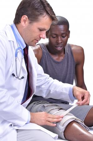 Mannelijke arts beveiligt been brace op jonge zwarte mannelijke atleet op een witte achtergrond Stockfoto