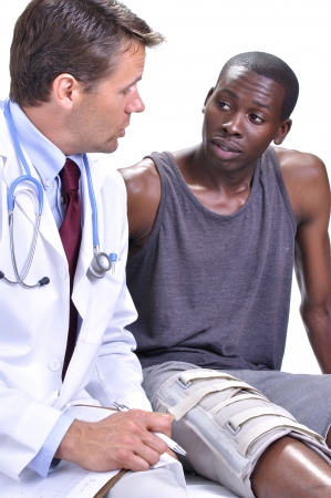 injured knee: Medical doctor meets with young black male patient with leg brace in clinic with white background Stock Photo