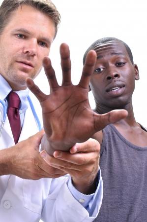 şişme: Beyaz doktor beyaz arka plan üzerinde uzun el ve genç atletik siyah hastanın bilek tendonları inceler