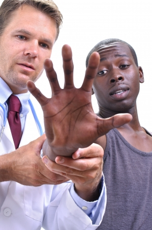 White doctor examines tendons of extended hand and wrist of young athletic black patient on white background