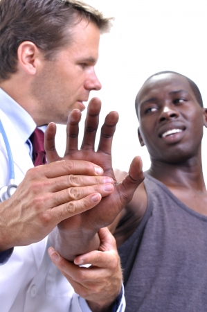 White medical doctor tests pain tolerance of young athletic black mans wrist on white background photo