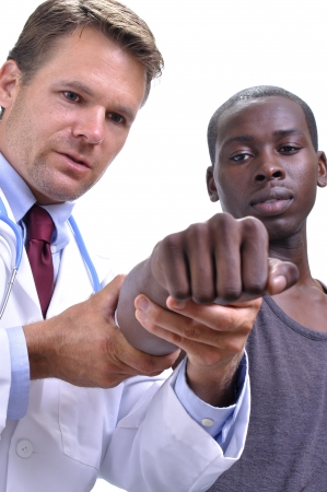 healing process: White doctor stretches out young black patients arm to examine healing process