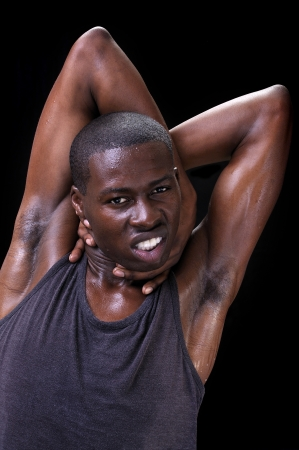 unrest: Portrait of young athletic black man with arms tangled behind head as he grabs his neck displaying anxiety and unrest on black background Stock Photo