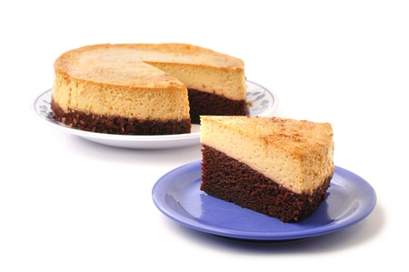 glycemic: Slice of layered chocolate Mexican flan on plate next to whole pie on white background