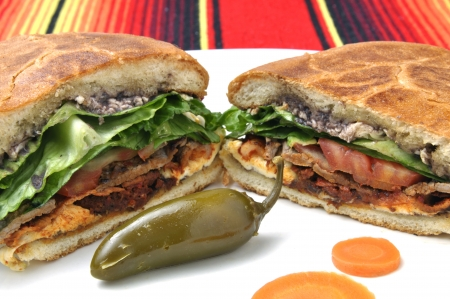 Closeup of halved Mexican torta sandwich with toasted bun and jalapeno pepper on plate over colorful tablecloth Stock Photo