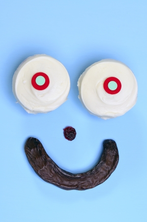 carob: Delicious smiley face made of cupcake eyes, cranberry nose, and carob pod smile on blue table