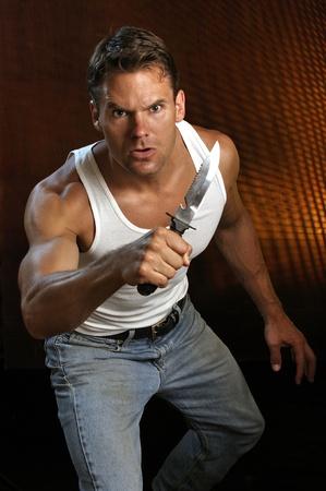 batidora: Hombre de raza caucásica muscular produciendo un gran cuchillo de supervivencia se prepara para atacar