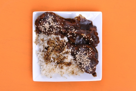 Top view of square plate of chicken and white rice topped with dark mole sauce and sesame seed on orange table Zdjęcie Seryjne