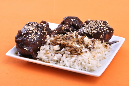 Traditional Mexican dish of chicken and white rice topped with dark mole sauce and sesame seed on orange table
