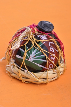 oaxaca: Typical Mexican handicraft mezcal container made of black clay from Oaxaca, Mexico on orange table