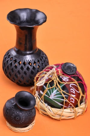 oaxaca: Assortment of typical Mexican handicrafts made of black clay from Oaxaca, Mexico on orange table Stock Photo