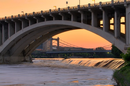 mississippi river: Beautiful Mississippi River flowing under arch of Third Avenue Bridge with Hennepin Avenue Bridge in background under golden sunset in Minneapolis